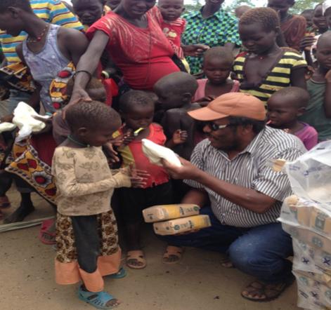 Edward issuing powdered milk & other relief supplies to children